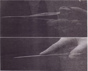 Needle holder is held with thumb and ring finger. Index finger extends along instrument for stability and control.