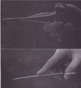 Needle holder is held by using thumb and ring finger in rings (top) and first and second finger to control instrument (bottom).