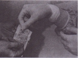 FIG. 5-4 Method of sterilely transferring double-wrapped sterile supplies from clean individual (ungloved hands) to sterilely gowned individual (gloved hands). Package is designed to be peeled open from one end, without touching sterile interior of package. Sterile contents are then promptly presented to recipient